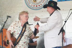 Bill White, himself an inductee this year, inducts Sheila Calthorpe into the Land O'Lakes Traditional Music Hall of Fame Saturday in Flinton.